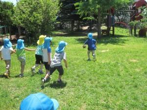 夏の園庭でサッカーする子どもたち